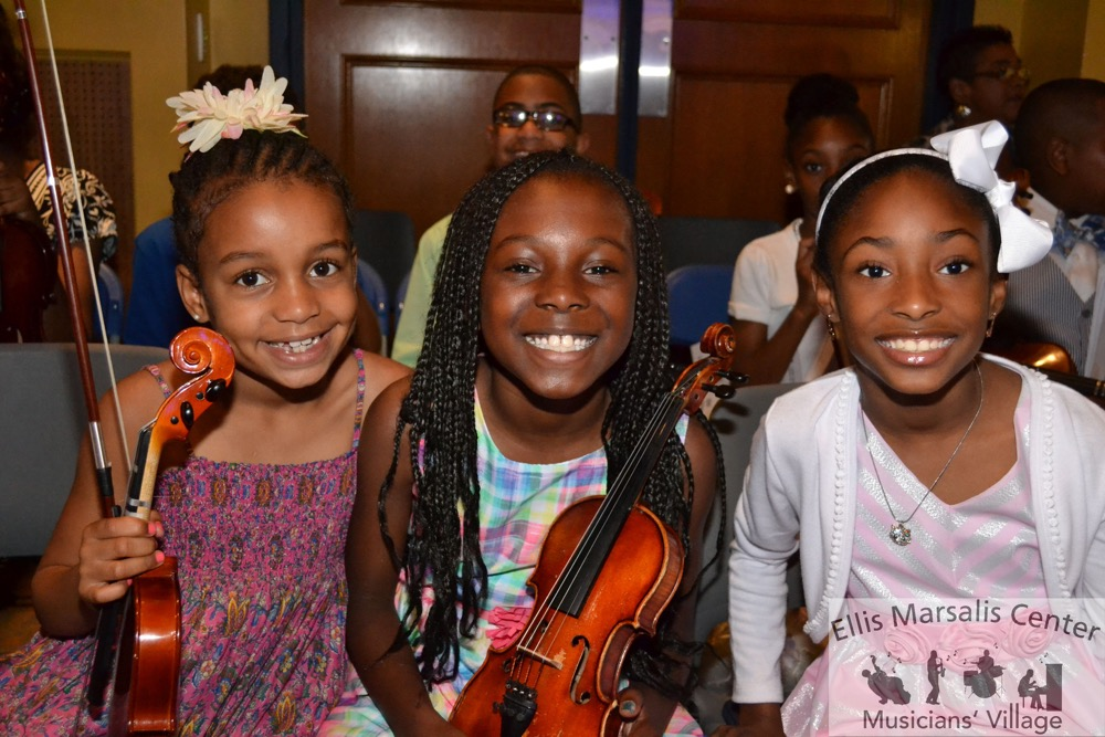 Three girls sit smiling with their violins, in an auditorium.